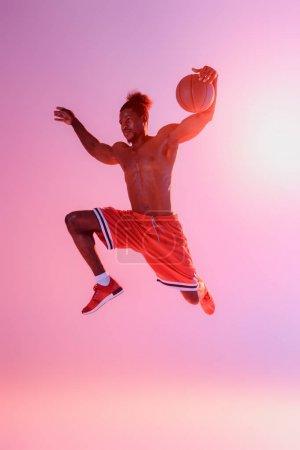 Photo pour Beau, sportif américain africain musculaire dans le saut rouge de short tout en jouant au basket-ball sur le fond rose et pourpre de gradient - image libre de droit