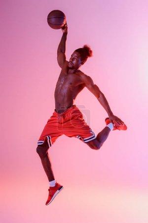 Foto de Deportista afroamericano con torso muscular jugando baloncesto en el fondo degradado rosa y púrpura - Imagen libre de derechos