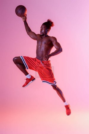 Photo pour Sportif sportif africain sportif américain en short rouge jouant au basket-ball sur fond de gradient rose et violet - image libre de droit