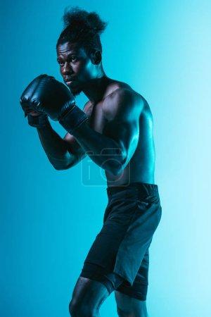 Photo pour Sportif américain africain confiant avec la boxe musculaire de torse sur le fond bleu - image libre de droit