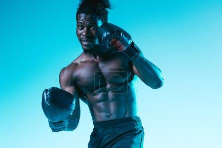 Photo pour Beau, musclé sportif afro-américain boxe sur fond bleu - image libre de droit