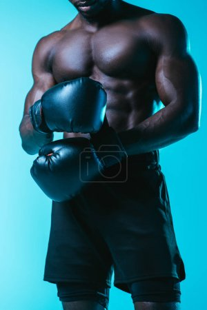 Photo for Partial view of shirtless, muscular african american sportsman in boxing gloves on blue background - Royalty Free Image
