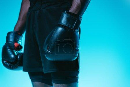 Photo pour Vue partielle du sportif américain africain dans les shorts et les gants de boxe sur le fond bleu - image libre de droit
