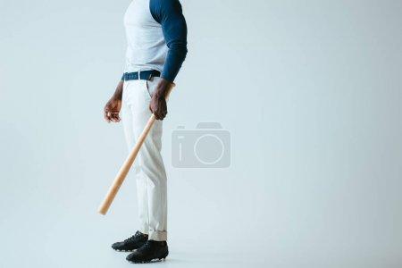 Photo pour Vue partielle du sportif américain africain avec la batte de base-ball sur le fond gris - image libre de droit