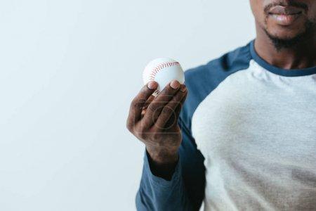 Photo pour Vue partielle du joueur de base-ball ameriican africain retenant la bille d'isolement sur le gris - image libre de droit