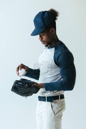 Foto de Apuesto deportista afroamericano en guante de béisbol sosteniendo bola aislada en gris - Imagen libre de derechos