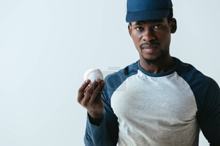 Photo for Handsome african american baseball player looking at camera while holding ball isolated on grey - Royalty Free Image