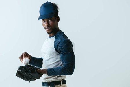 Photo pour Sportif américain africain confiant dans le gant de base-ball regardant la caméra d'isolement sur le gris - image libre de droit