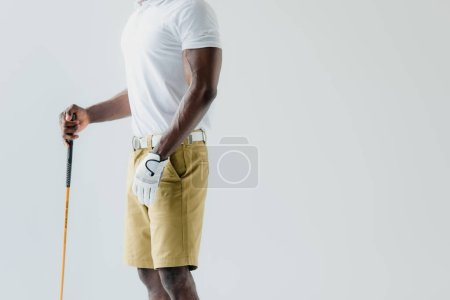 Photo pour Vue recadrée du sportif américain afrcan retenant le club de golf d'isolement sur le gris - image libre de droit