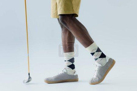 Photo pour Vue recadrée du sportif américain africain retenant le club de golf sur le fond gris - image libre de droit