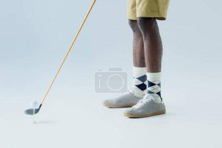Photo pour Vue recadrée du sportif américain africain jouant au golf sur le fond gris - image libre de droit