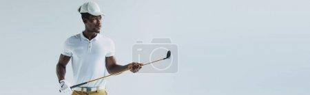 Photo pour Tir panoramique de beau sportif américain africain retenant le club de golf d'isolement sur le gris - image libre de droit
