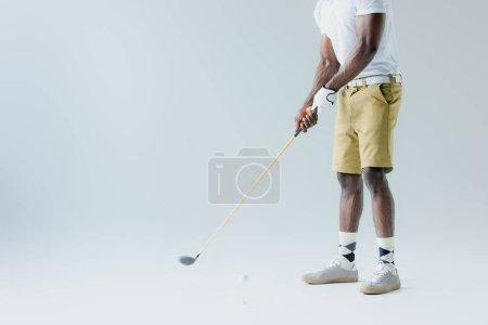 Photo pour Vue recadrée du sportif américain africain dans des shorts jouant au golf sur le fond gris - image libre de droit