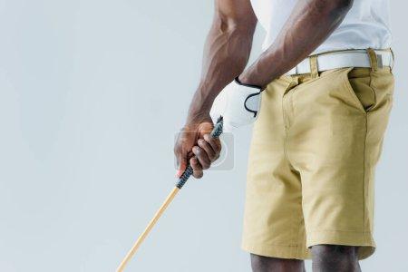 Photo pour Vue partielle du sportif américain africain dans le short jouant au golf d'isolement sur le gris - image libre de droit