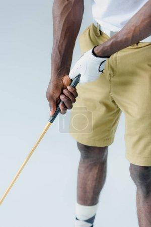 Photo pour Vue recadrée du sportif américain africain dans les shorts jouant au golf d'isolement sur le gris - image libre de droit