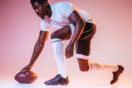 Photo for Young african american sportsman playing american football on pink background with gradient and yellow lighting - Royalty Free Image