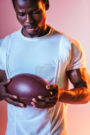 Photo for Handsome, young african american sportsman holding rugby ball on pink background with lighting - Royalty Free Image