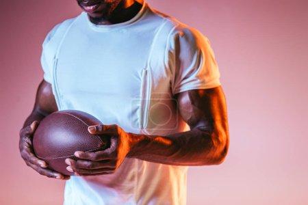Photo pour Vue recadrée du sportif américain afican retenant la bille de rugby sur le fond rose avec le gradient et l'éclairage - image libre de droit