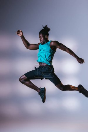 Photo for Young, athletic african american sportsman jumping on grey background with lighting - Royalty Free Image