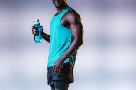 Photo for Cropped view of muscular african american sportsman holding sports bottle on grey background with lighting - Royalty Free Image