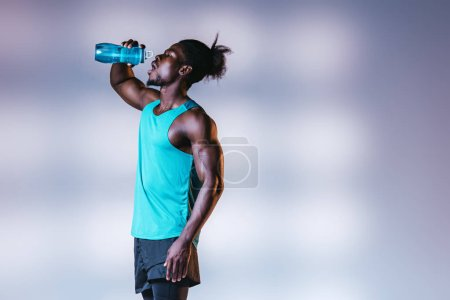 young african american sportsman drinking from sports bottle on grey background with lighting