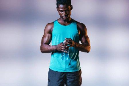 Photo pour Sportif américain sérieux africain retenant la bouteille de sports sur le fond gris avec l'éclairage - image libre de droit
