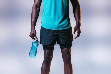 Photo for Cropped view of african american sportsman in shorts holding sports bottle on grey background with lighting - Royalty Free Image