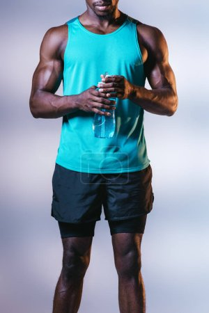 Photo for Partial view of african american sportsman in shorts holding sports bottle on grey background with lighting - Royalty Free Image
