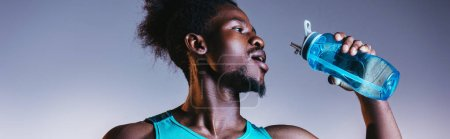 Photo for Panoramic shot of african american sportsman drinking from sports bottle on grey and blue gradient background with lighting - Royalty Free Image
