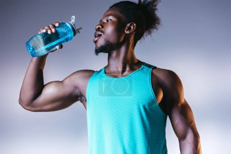 Photo for Young, muscular african american sportsman drinking from sports bottle on grey and blue gradient background with lighting - Royalty Free Image