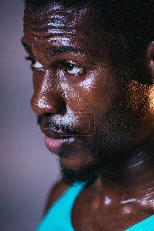Photo for Portrait of handsome african american sportsman with sweaty face on dark background - Royalty Free Image