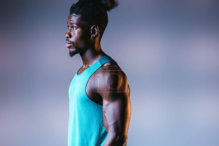 Photo for Handsome, muscular african american sportsman looking away on grey background with lighting - Royalty Free Image