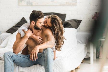 Photo pour Foyer sélectif de deux personnes amoureuses étreignant tout en étant assis dans le lit - image libre de droit
