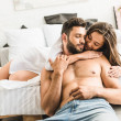 Young girl lying in bed and hugging man while guy ...