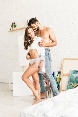 Photo pour Homme torse nu étreignant la petite amie de dos tandis que la fille restant avec les yeux fermés - image libre de droit