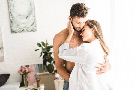Photo pour Jeunes couples sexy étreignant l'un l'autre avec l'appel d'offres tout en restant près de la fenêtre - image libre de droit