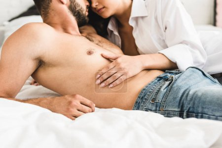 Photo pour Vue recadrée de couples sexy se trouvant dans le lit tandis que la fille touchant le torse de l'homme - image libre de droit