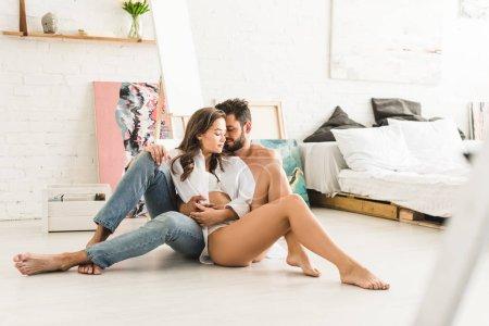 Photo pour Foyer sélectif de couple sexy assis sur le sol tandis que l'homme câlin fille de dos - image libre de droit