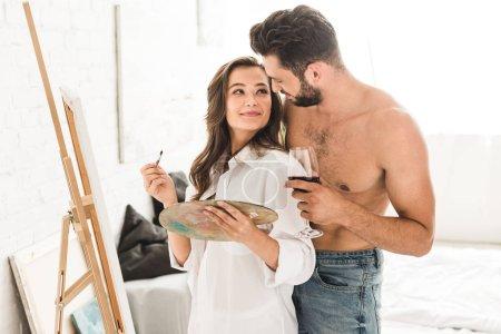 Photo pour Jeune artiste dessin tandis que copain tenant verre avec du vin et câlin fille de dos - image libre de droit