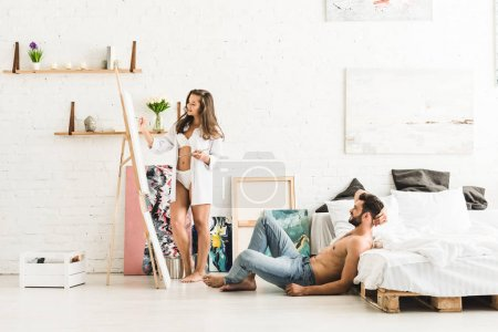 Photo for Full length view of girl drawing with brush and man sitting on floor near bed - Royalty Free Image