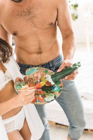 Photo for Sexy girl in white underwear holding brush and palette while man adding green paint on palette - Royalty Free Image