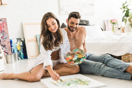 Photo for Happy couple sitting on floor while girl paiting and man looking at process - Royalty Free Image