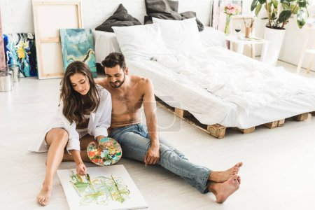 Photo for Full length view of happy couple sitting on floor while girl paiting and man looking at process - Royalty Free Image