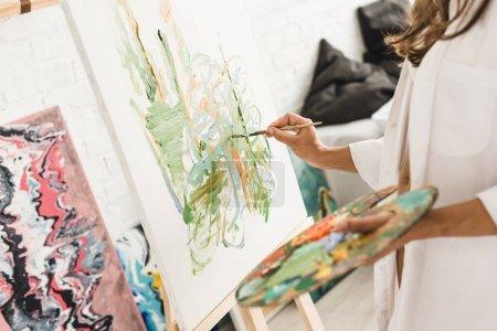 Photo pour Vue recadrée du dessin de jeune fille avec pinceau et palette de tenue - image libre de droit