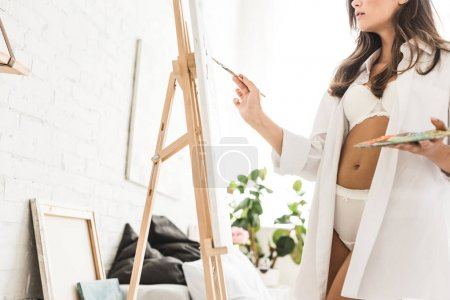 Photo for Cropped view of  sexy girl drawing with brush and holding palette - Royalty Free Image