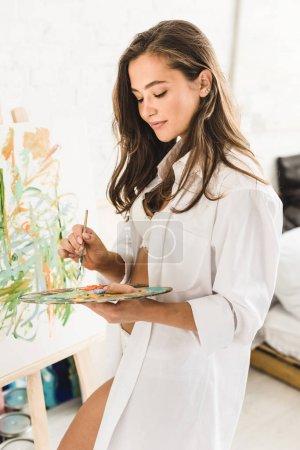 Photo pour Dessin sexy belle fille avec le pinceau et la palette de fixation - image libre de droit