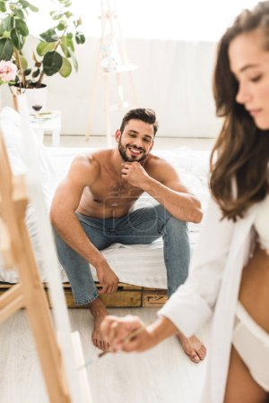 Photo for Selective focus of sexy girl drawing while shirtless man smiling and sitting in bed - Royalty Free Image