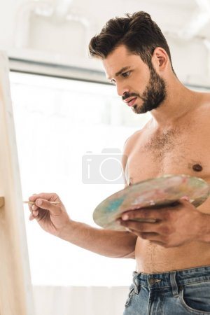 Photo for Sexy shirtless man drawing with brush and holding palette - Royalty Free Image