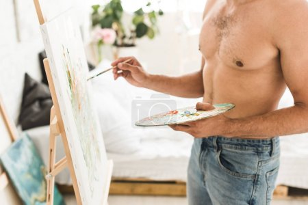 Photo for Cropped view of sexy shirtless man drawing with brush and holding palette - Royalty Free Image