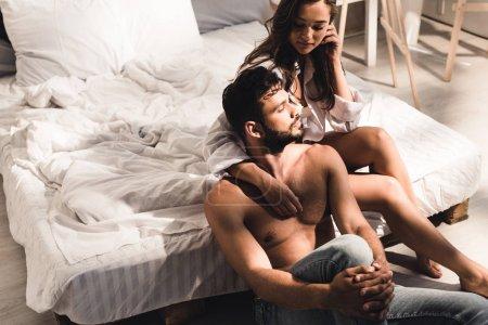 Photo pour Homme torse nu assis près du lit tandis que la fille assise dans le lit et regardant le gars - image libre de droit